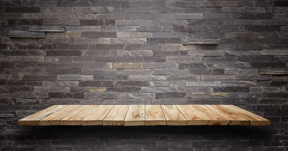 Wooden shelf on a brick wall